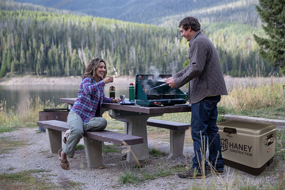 Man and woman cooking food on coleman classic stove on concrete table