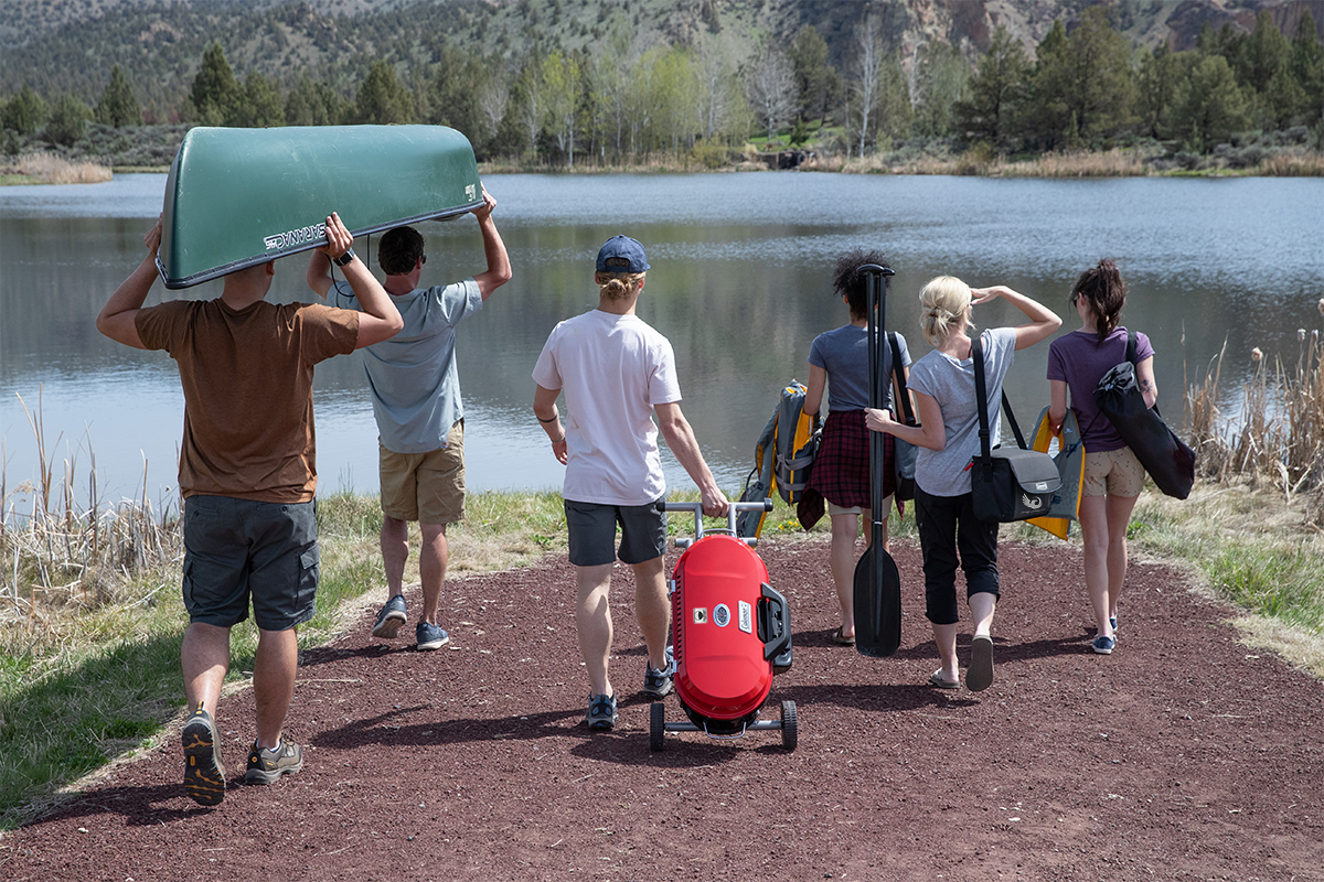 2 men carrying canoe, 1 man pulling Coleman RoadTrip grill, 1 woman carrying life jackets, 1 woman carrying collapsible cooler, 1 woman carrying life jacket and chair down a path towards a body of water