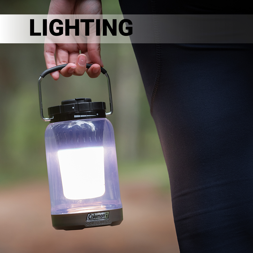 Person carrying lighted Coleman OneSource 600L Lantern in wilderness