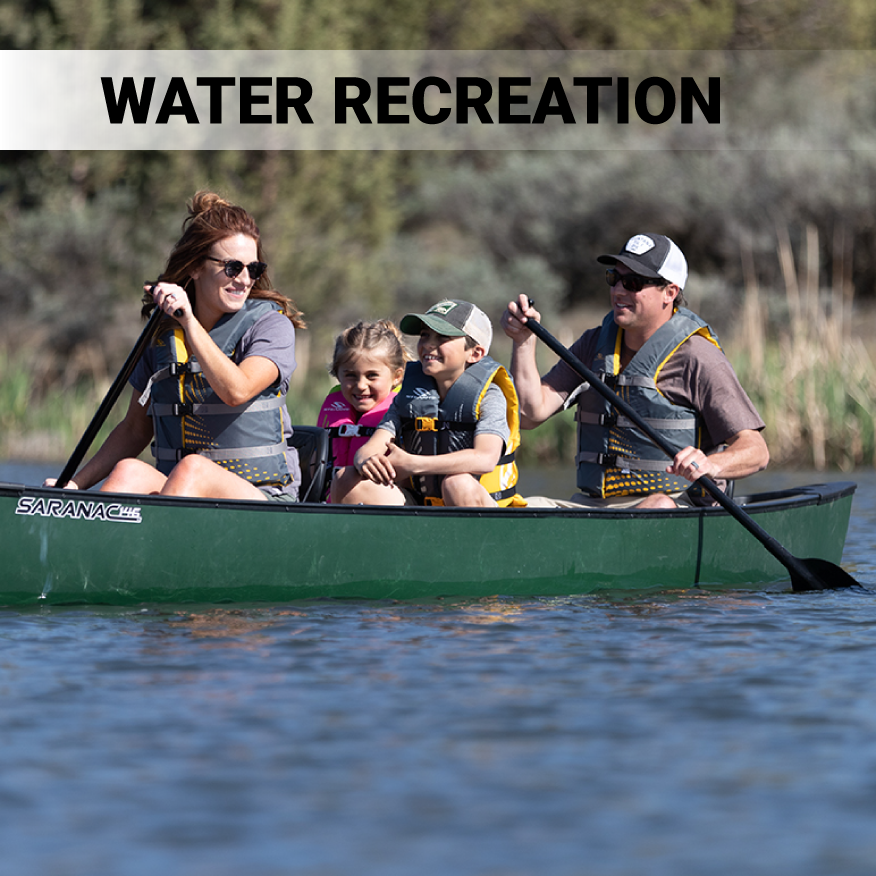 Woman, girl, boy and male family litting in green canoe with Stearns Classic Life Jackets on water.
